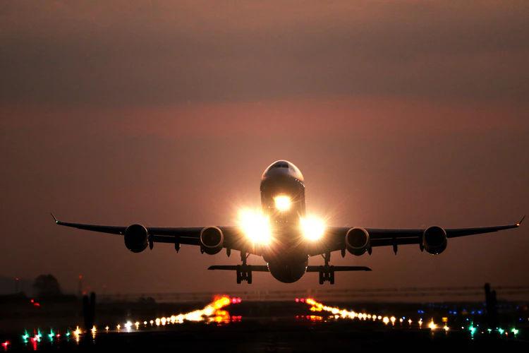 Samolot wznoszący się nad oświetlonym pasem startowym.