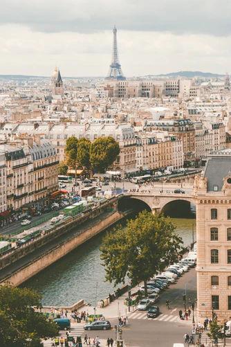 Widok z okna na panoramę Paryża z wieżą Eiffla w tle.